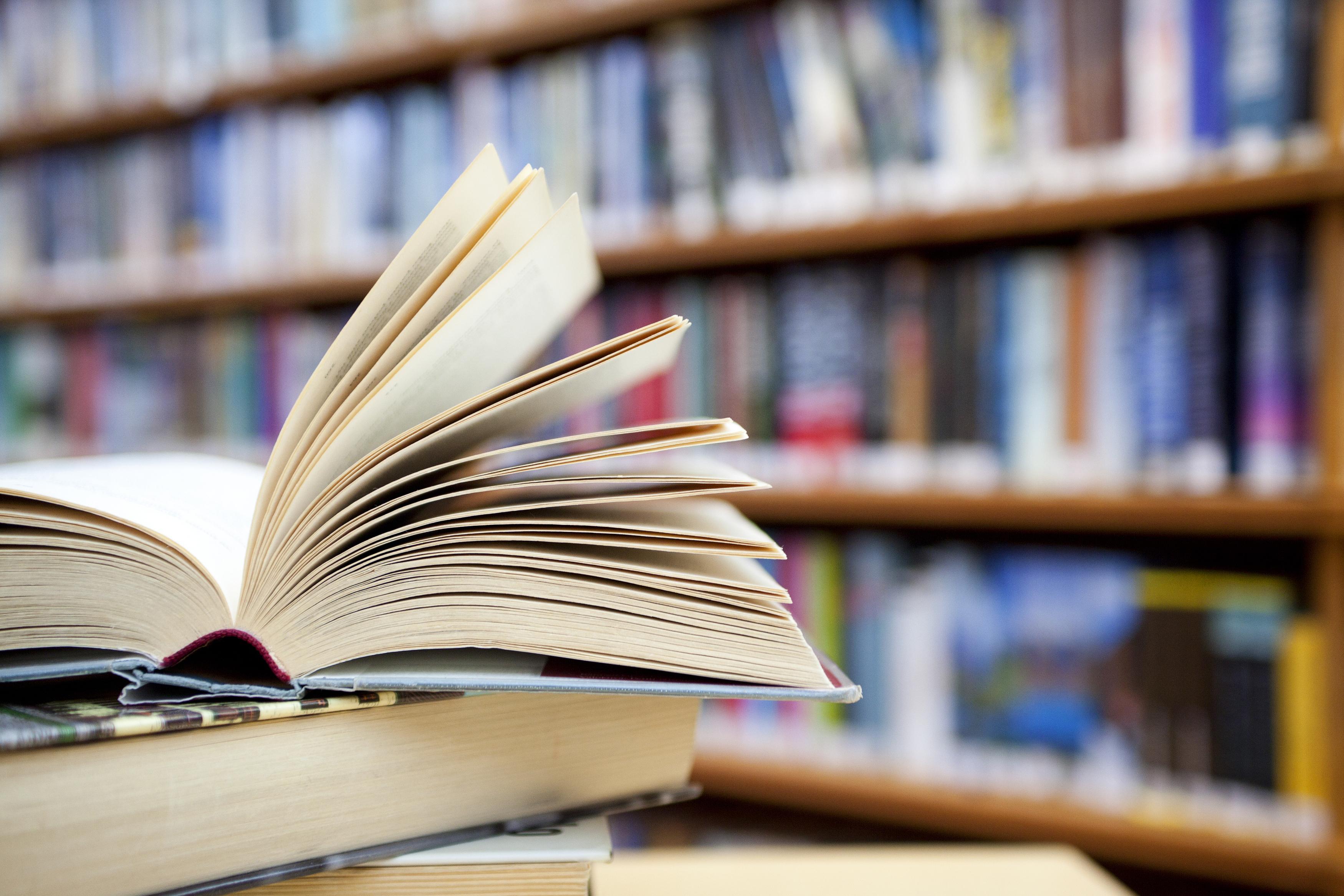 Bücherregal und aufgeschlagenes Buch