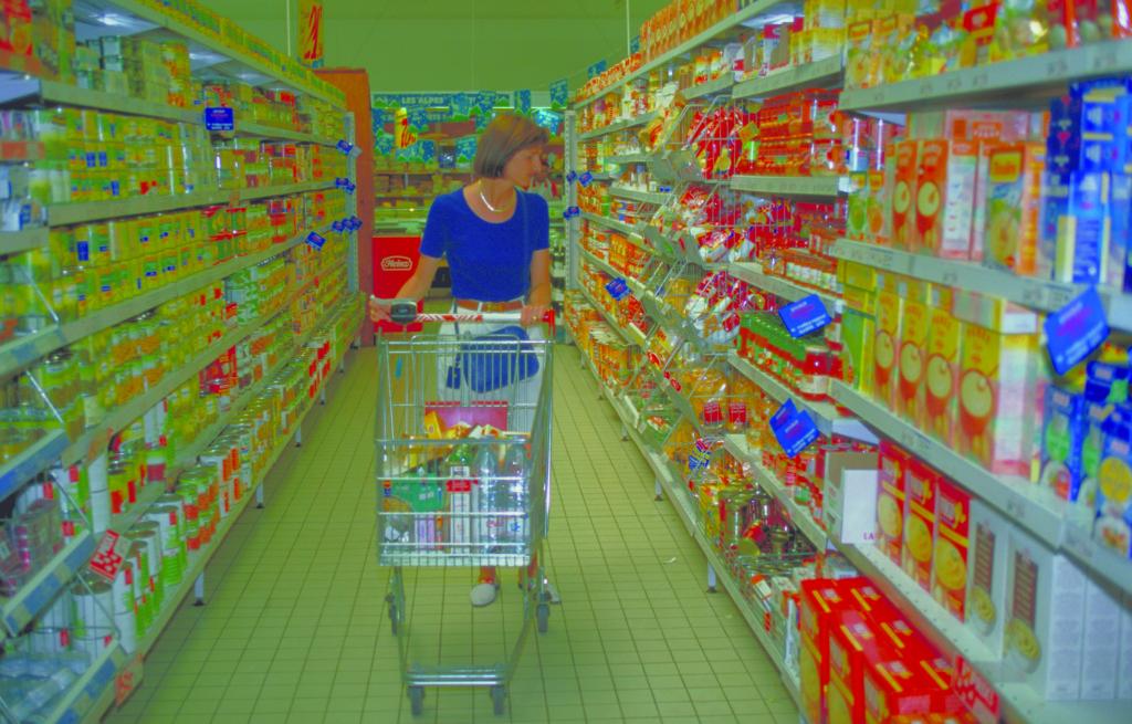 Frau schiebt Einkaufswagen durch Supermarkt
