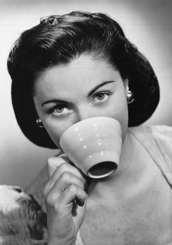 Frau mit 50er Frisur führt eine Tasse Kaffee zum Mund